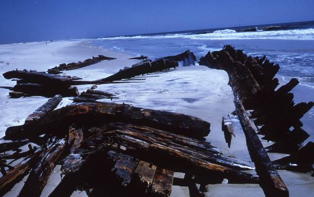 A shipwreck exposed in the surf after a storm.