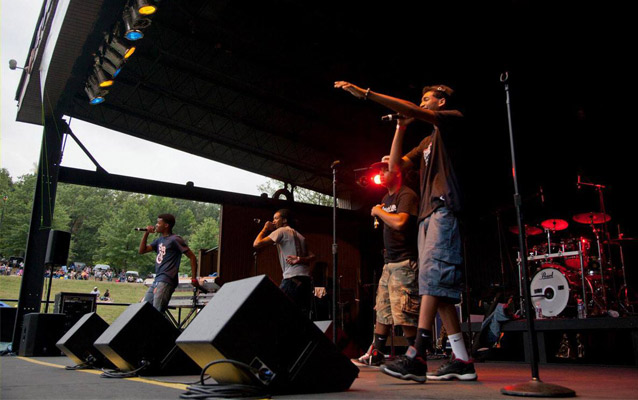 Youth perform on stage at a concert