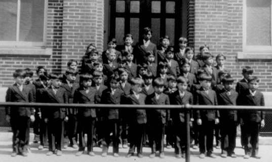 Children stand in suits in front of a schoolhouse