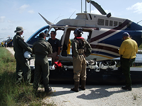 A group standing by a helicopter receives a safety briefing.