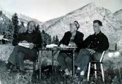 black and white image of three people at an outdoor table