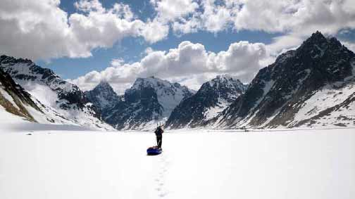 a person skiing across a vast glacier with snowy mountains in the distance