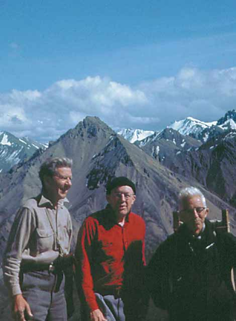 three old men standing on a mountain top