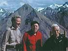 three men standing on a mountain top
