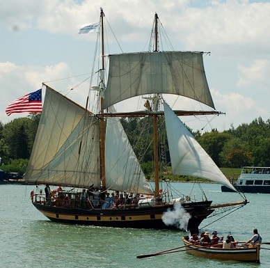 A rowboat approaches a two-masted sailing ship flying the American flag.