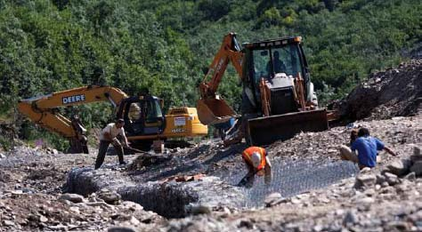 people and construction equipment working in a rocky stream bed