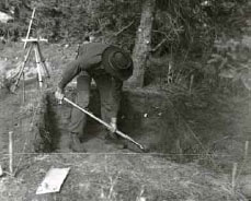 black and white image of a man digging a hole