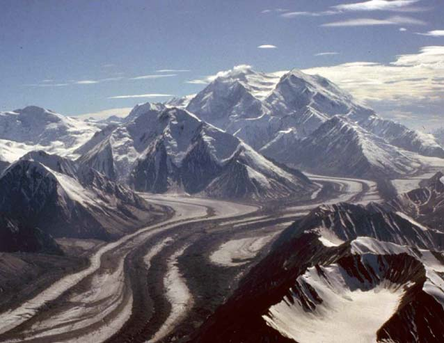 aerial view of a vast white mountain with numerous glaciers and smaller mountains