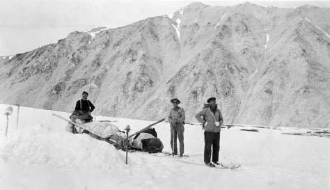 three men stnading on a snowy mountainside pulling a large sled