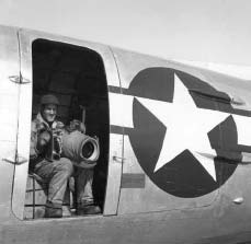 Man sitting with a giant camera in an open door of an aluminum plane