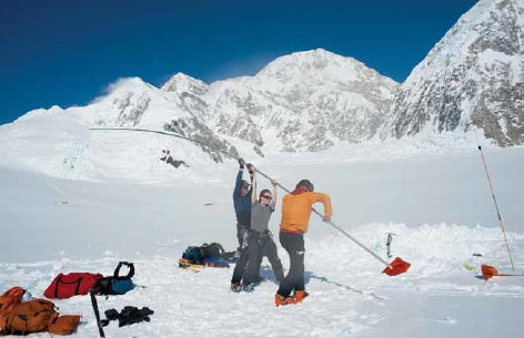 two people placing a long pole into the snow, snowy mountains in the distance