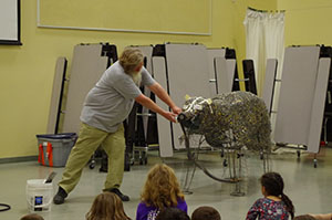 A man shows students how a trash-art-bear sculpture was created