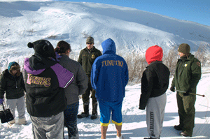Students gather around park rangers while backdropped by a snowy mountain