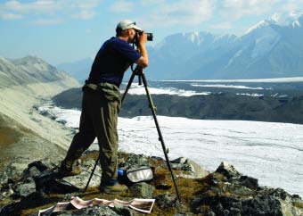 man standing on a ridge taking photos of a glacier