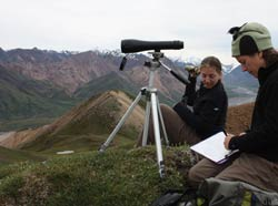 two women sitting on a mountaintop with a spotting scope