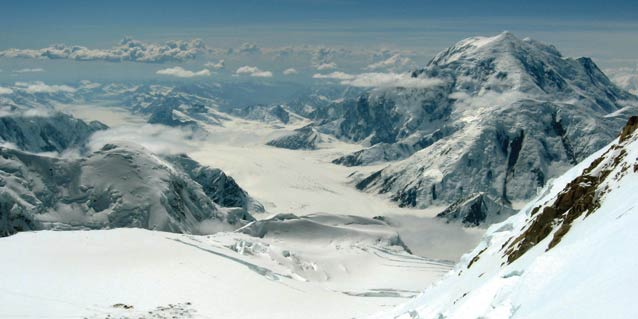 impressive vista of steep snowy mountains and large, winding glaciers