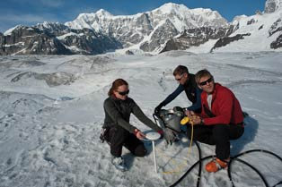 three people crouched near each other on a glacier under blue skies
