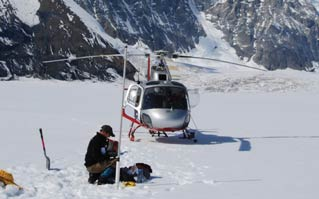 man kneeling in snow, near a helicopter