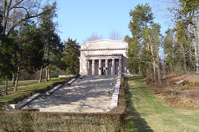 Broad stairs ascend up the slope toward the memorial, stone with a line of columns across the front.