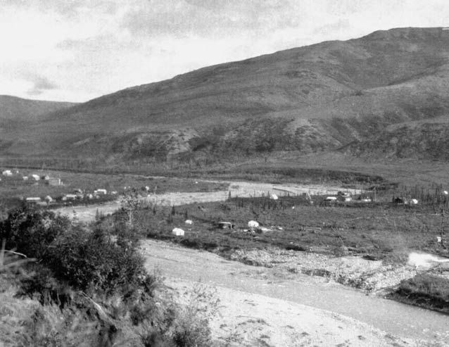 black and white image of a hill overlooking a river valley with scattered buildings
