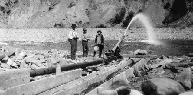 back and white image of three men standing near a hydraulic tube spewing water into a creek
