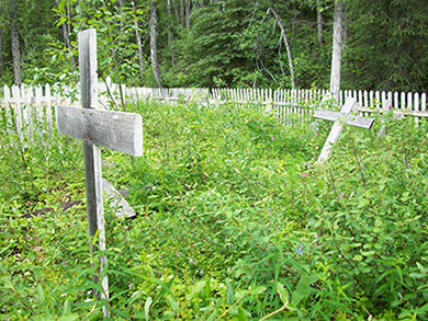 Wooden crosses stand at various angles in an overgrown plot, surrounded by a white picket fence.