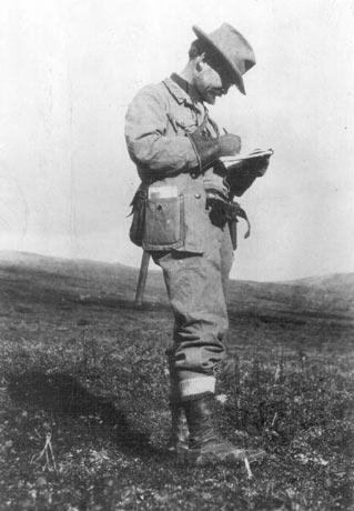black and white image of a man writing in a notebook while standing on a hillside