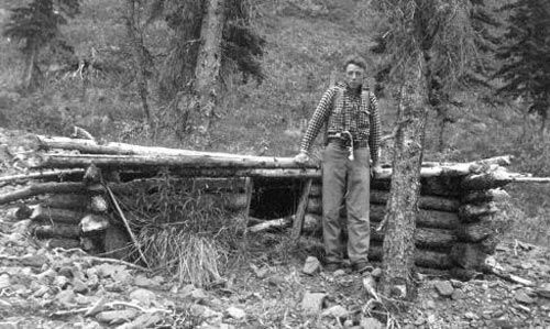 black and white image of a man standing near a very small log cabin