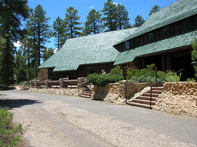 A rustic lodge with a broad green roof is surrounded by stone retaining walls and tall pines.