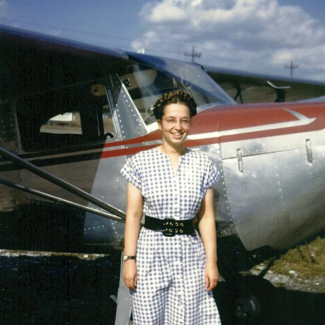 woman in a dress standing next to a 1940s-era plane