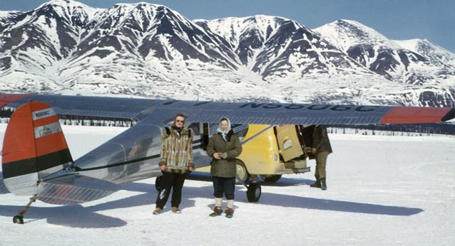 Two women standing near a small plane that is parked on a frozen lake or snowy landing field