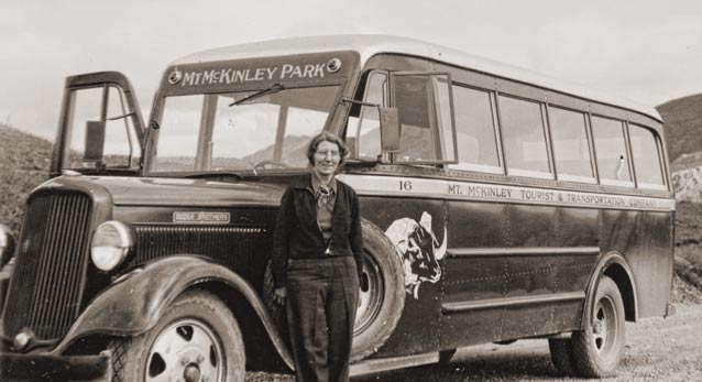 black and white historic image of woman standing near a bus