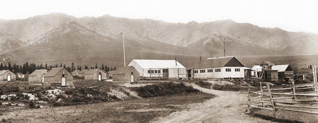 sepia toned image of numerous small cabins and two larger buildings with mountains in the distance