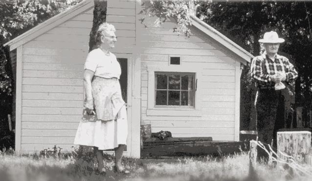 black and white image an elderly man and woman near a white colored house
