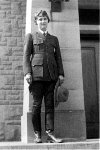 woman in ranger uniform standing by a wall holding her hat