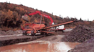 large machine scraping up earth and dumping it into a sluice