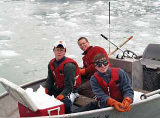three young men in a boat pulling ice out of the water