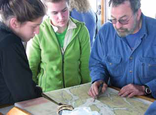 two teens looking at a map with an older man