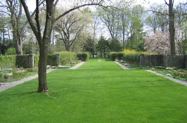 An expanse of manicured green lawn flows through the center of the formal gardens.
