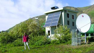 woman standing in front of a small white building with big solar panels on it