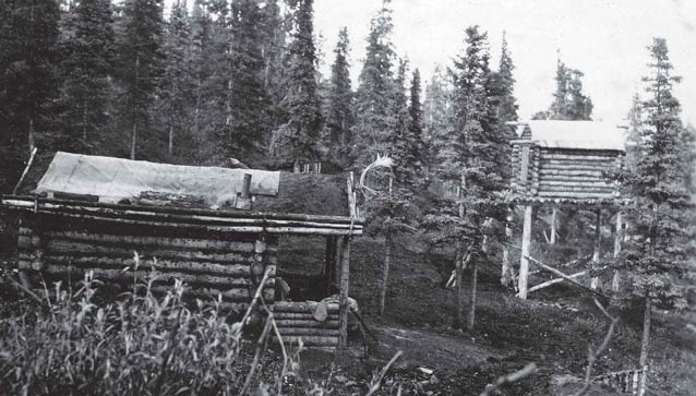 historic black and white image of a log cabin and tall cache