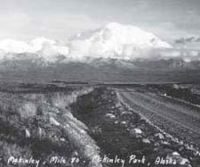 historic image of a dirt road with a huge snowy mountain in the background