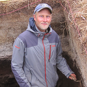 Researcher stands in archaeological dig with tools in hand