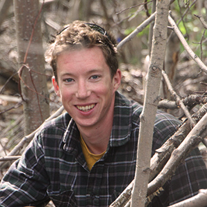 Researcher crouches among trees