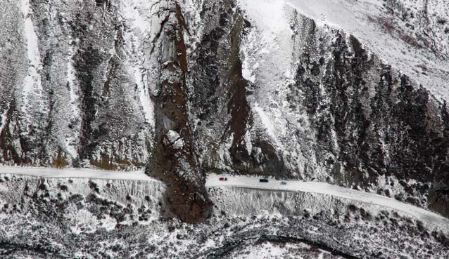 snow-dusted hillside with a large landslide across a snowy road, three cars parked nearby