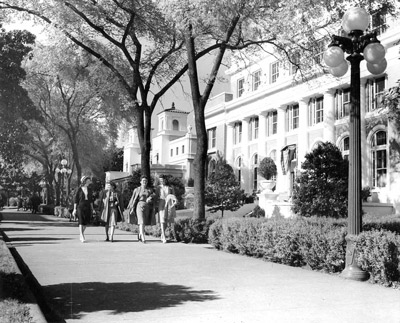 Four young women in 1940s-style skirts and jackets smile as they walk down a tree-lined walkway.