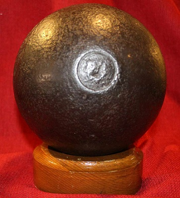 Cannonball sitting on wood stand