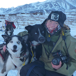 Musher hugs two sled dogs