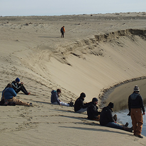 Students sit on the edge of a sand dune