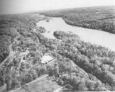 An aerial view of the landscape shows the river, canal clearing in the trees, and amusement park.